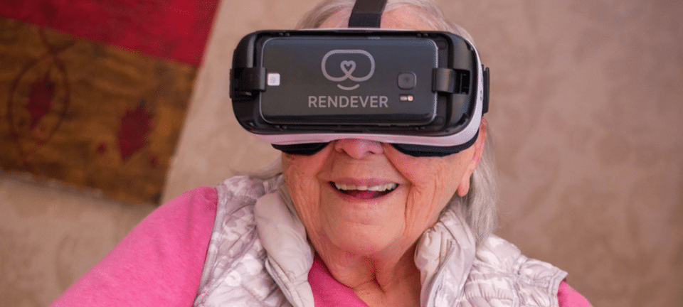 Older woman smiling as she uses VR device