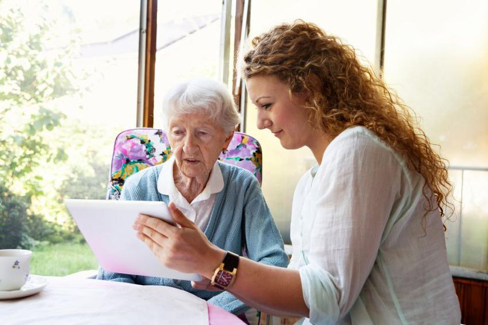 Woman helping senior with laptop