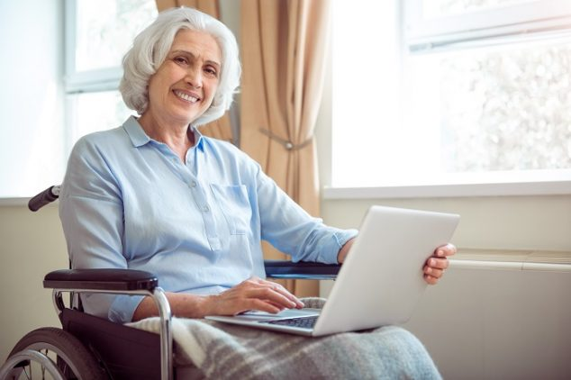 Elderly woman sitting in wheelchair, using laptop and smiling at camera