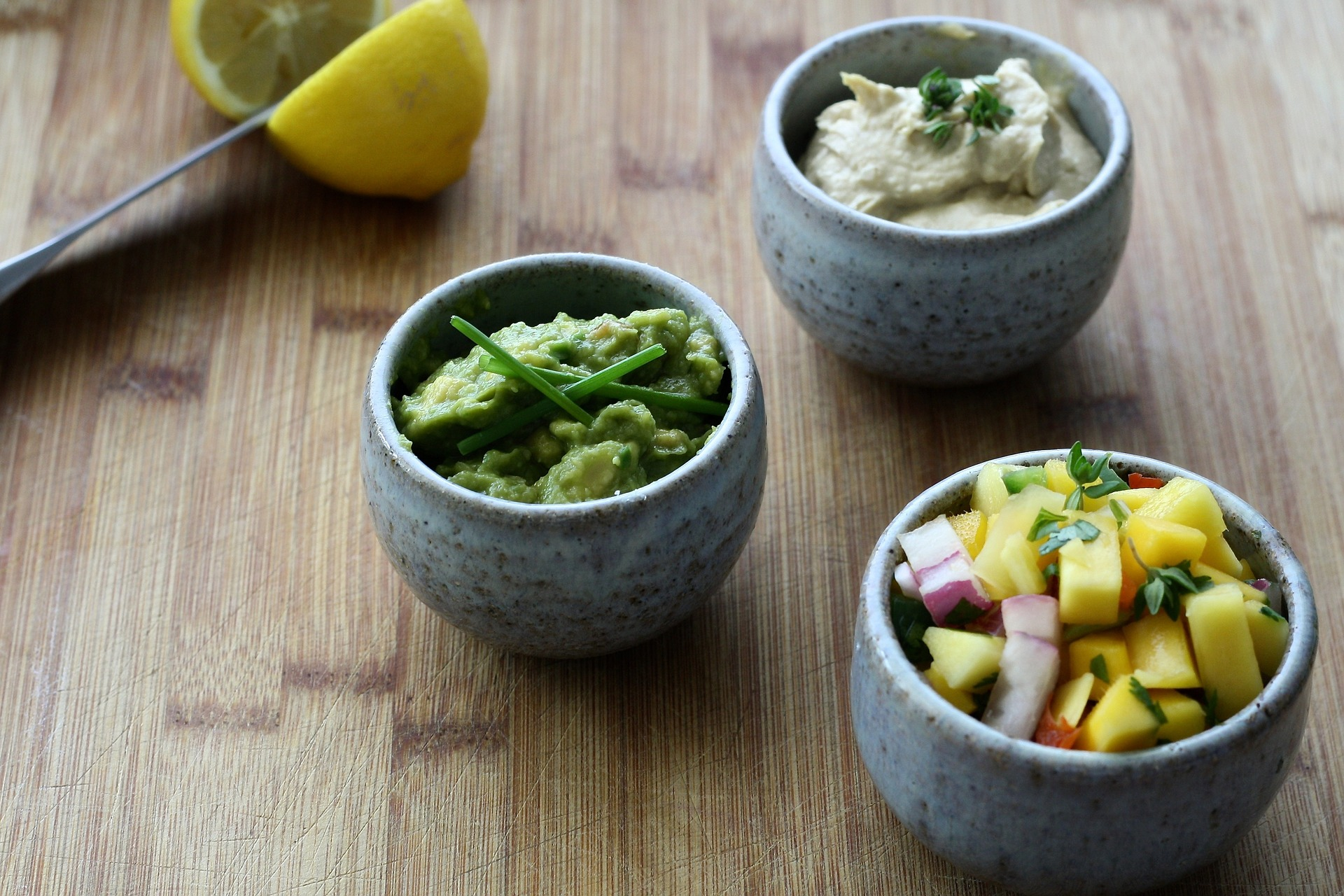 Three bowls with different ingredients. Main bowl is mango salsa.