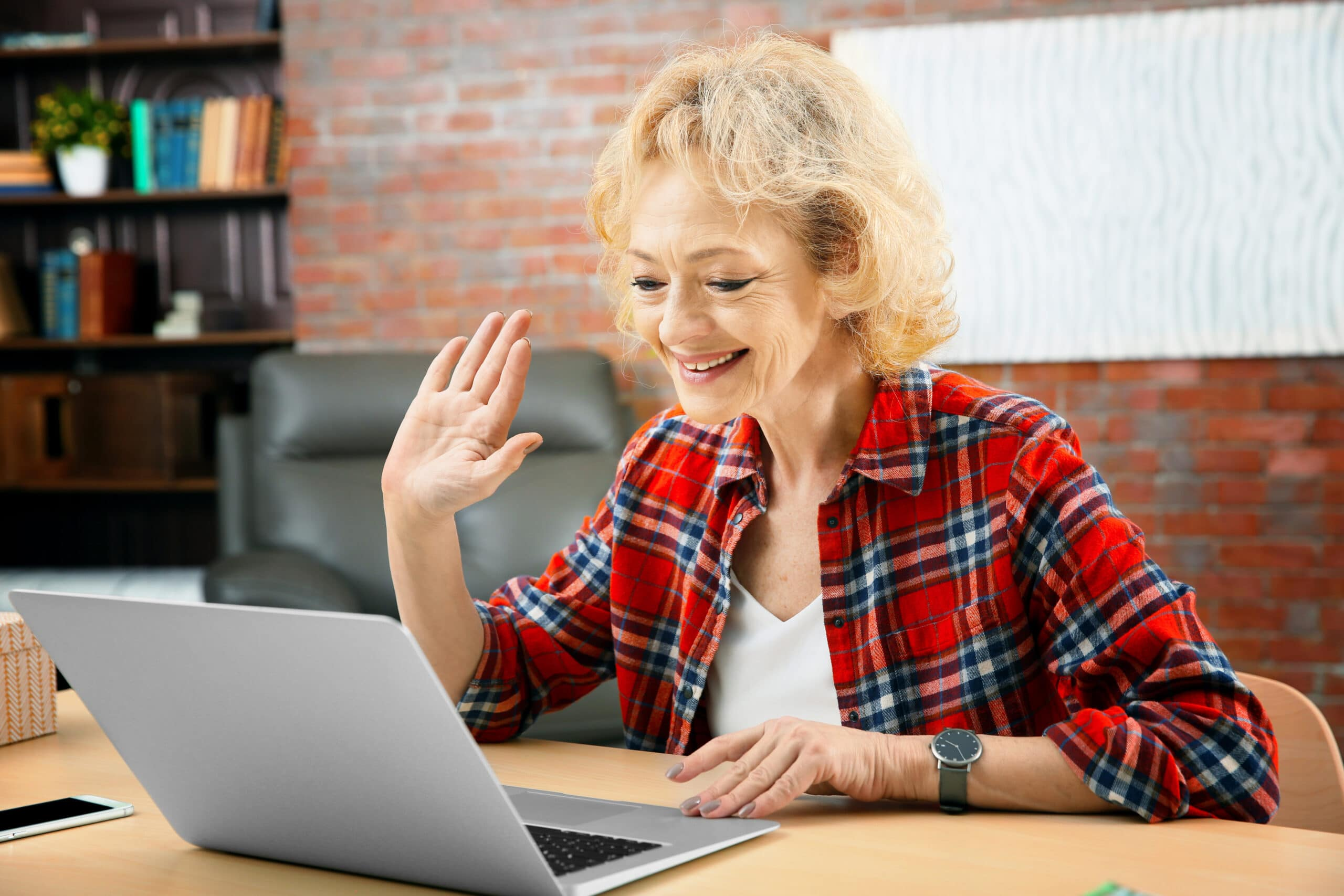 Senior woman engaging in distance learning using laptop at home
