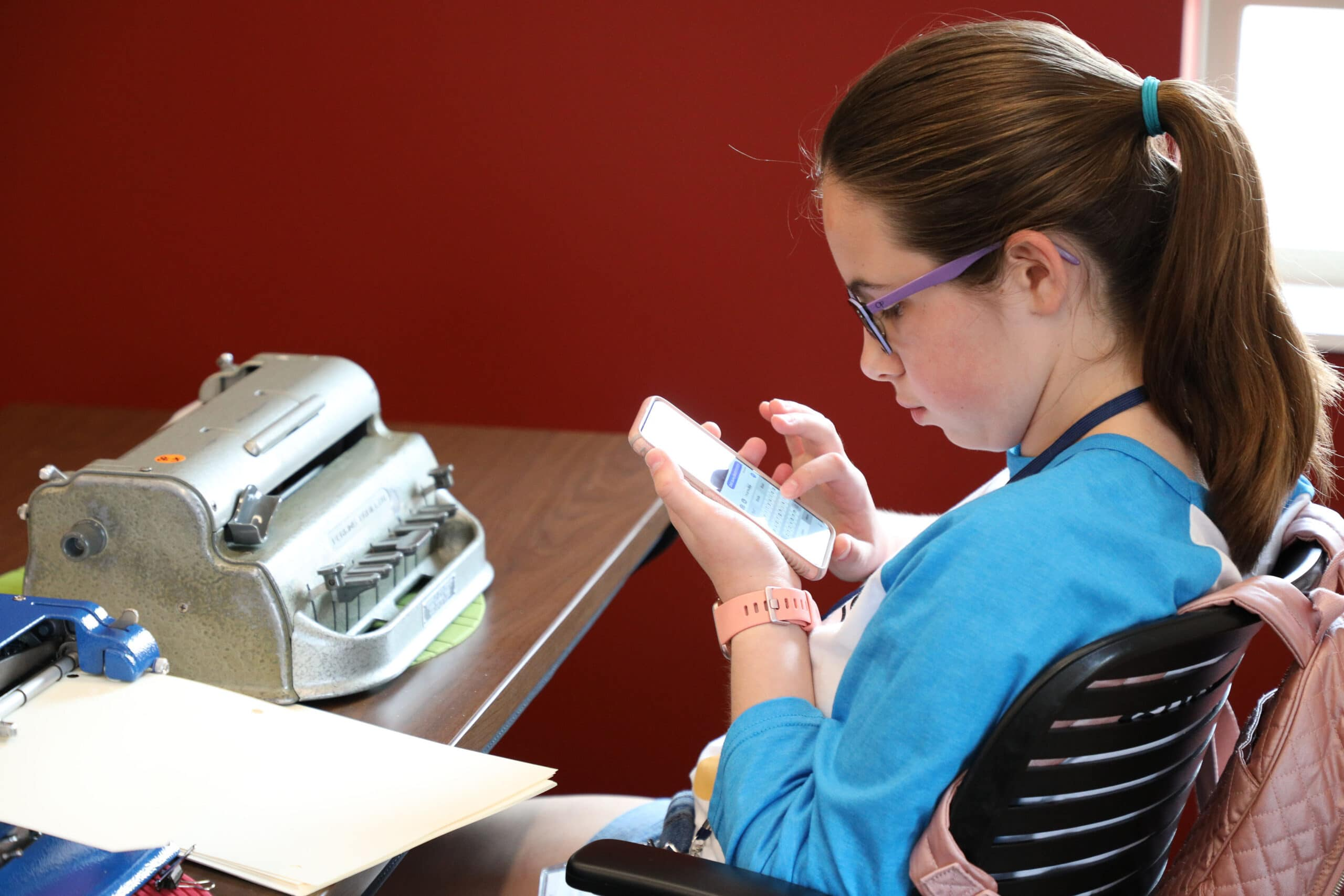 Female Braille Challenge finalist scrolling on iPhone with brailler on table infront of her.