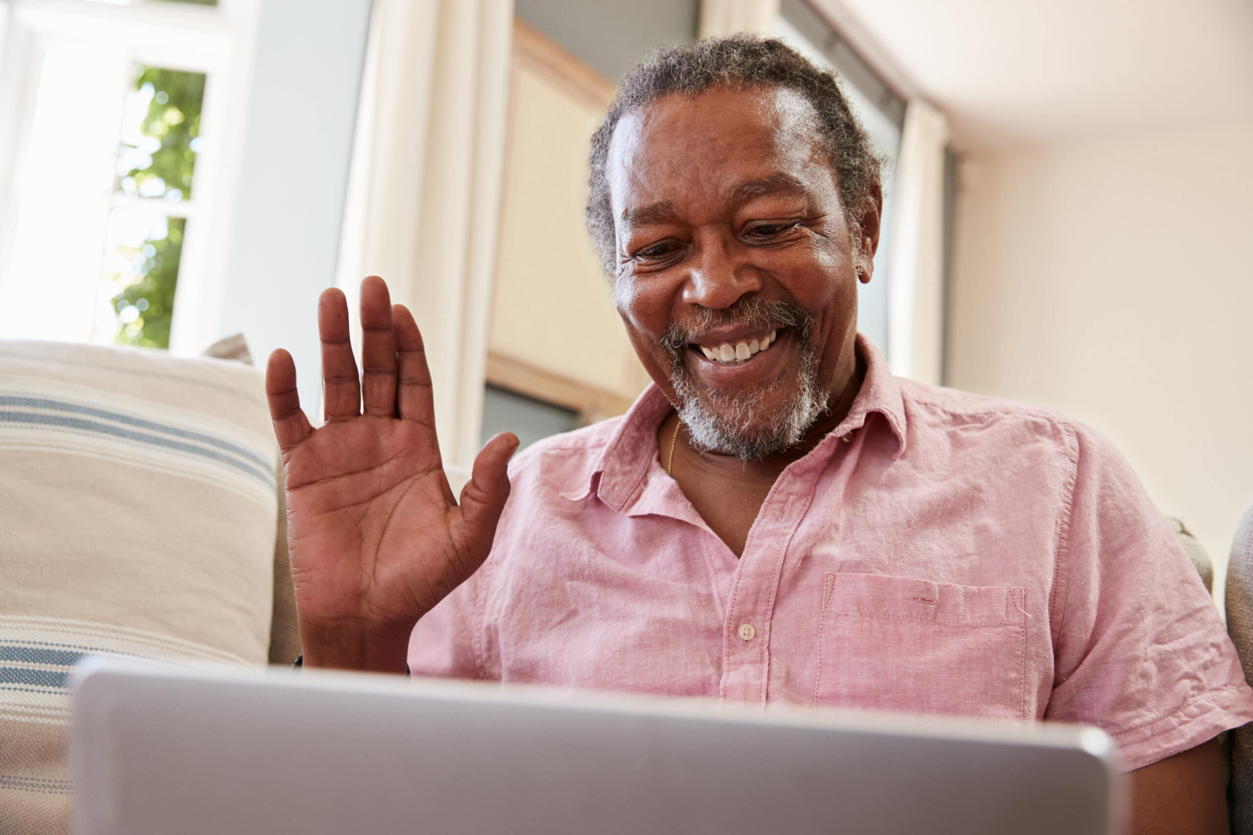 Older man smiles and raises his hand while on a remote session on the computer