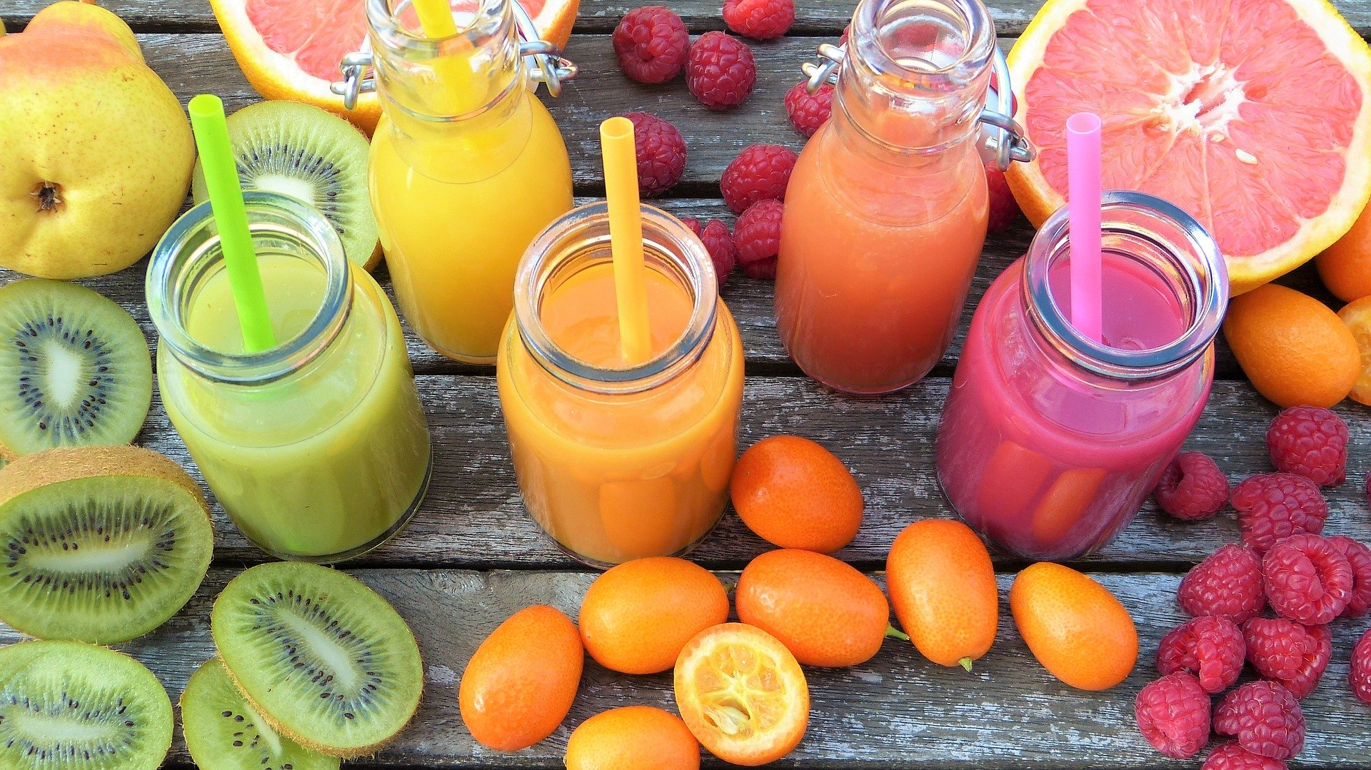 Four glasses of juice surrounded by a variety of cut fruit