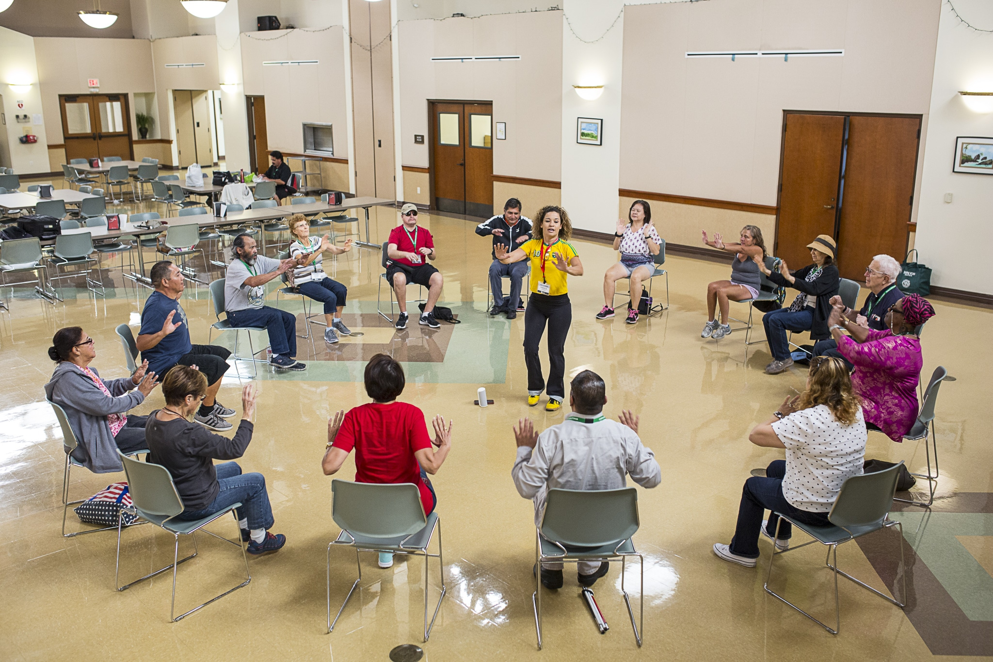 15 people sitting in a circle following the movement directions of the instructor in the middle.