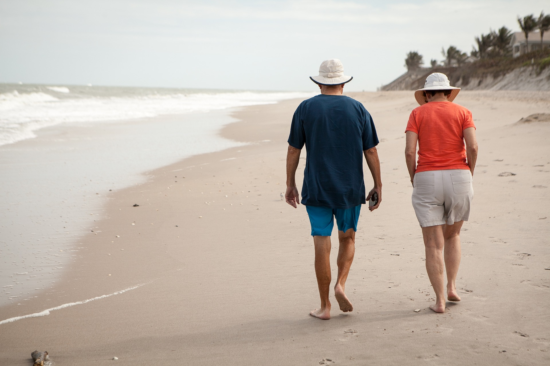 Man and woman walking on a sandy beach.