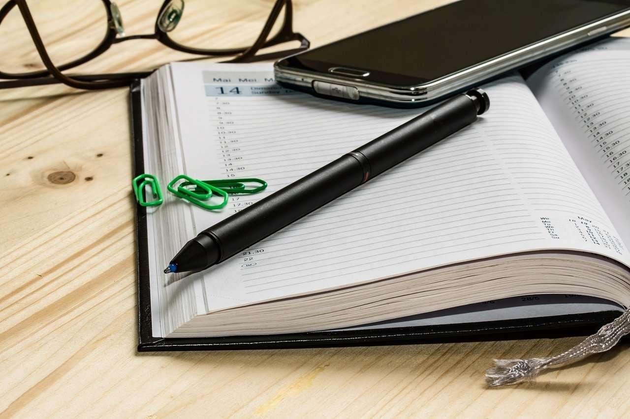 Agenda, pen, green paper clips, glasses and cellphone rest on desk