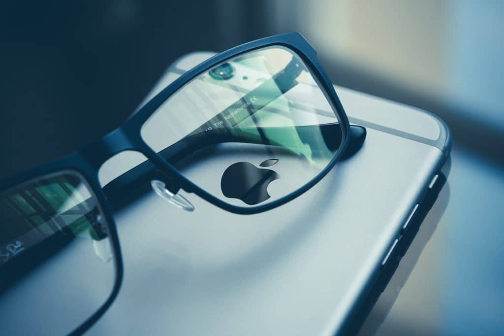 Eye glasses resting on top of an iphone