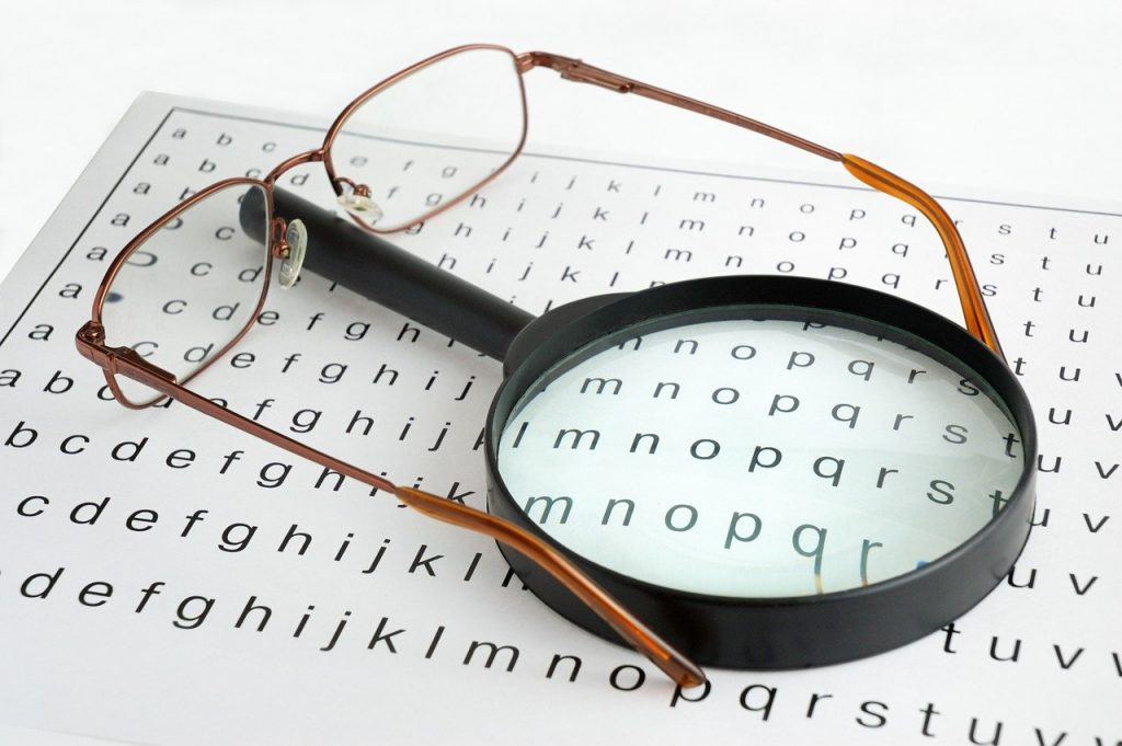 Magnifier and glasses resting on sheet of letters