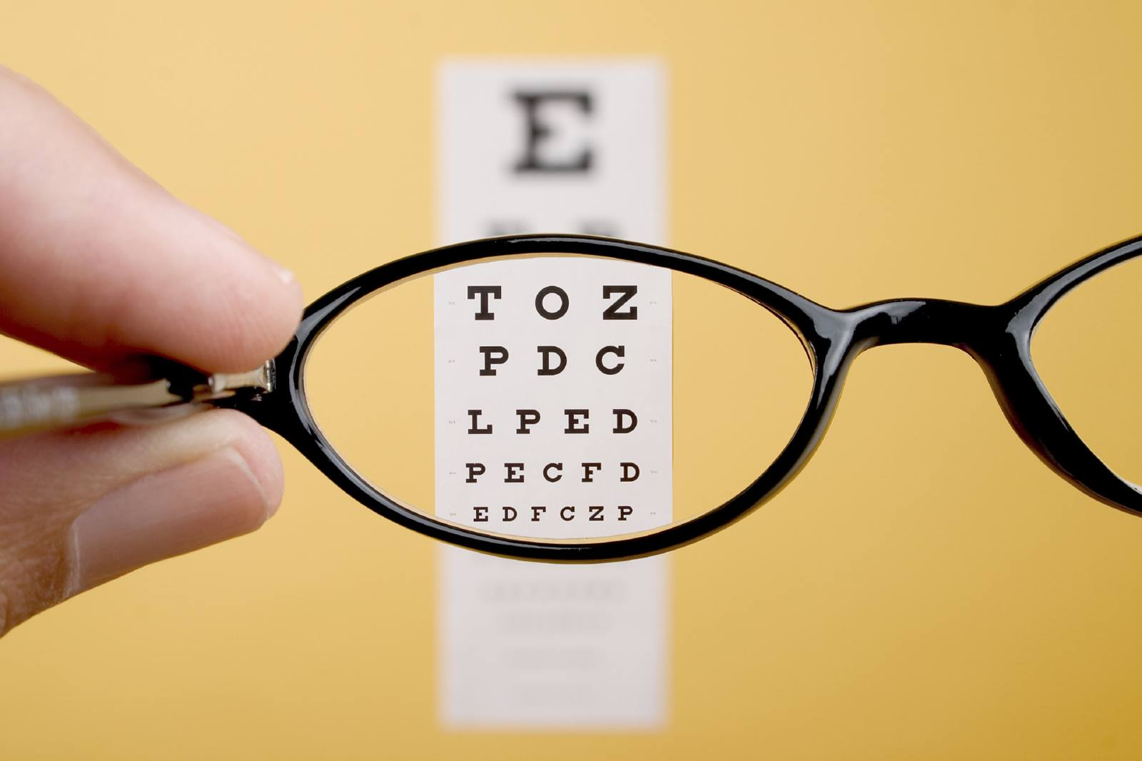 A pair of eyeglasses being held up in front of an eye chart