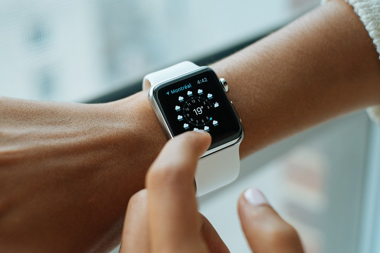 Close up of woman's apple watch on her wrist. Information is showing weather for Montreal.
