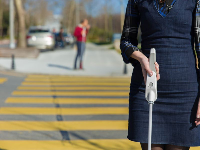 Woman holding the weWalk cane as she stands in front of a crosswalk.
