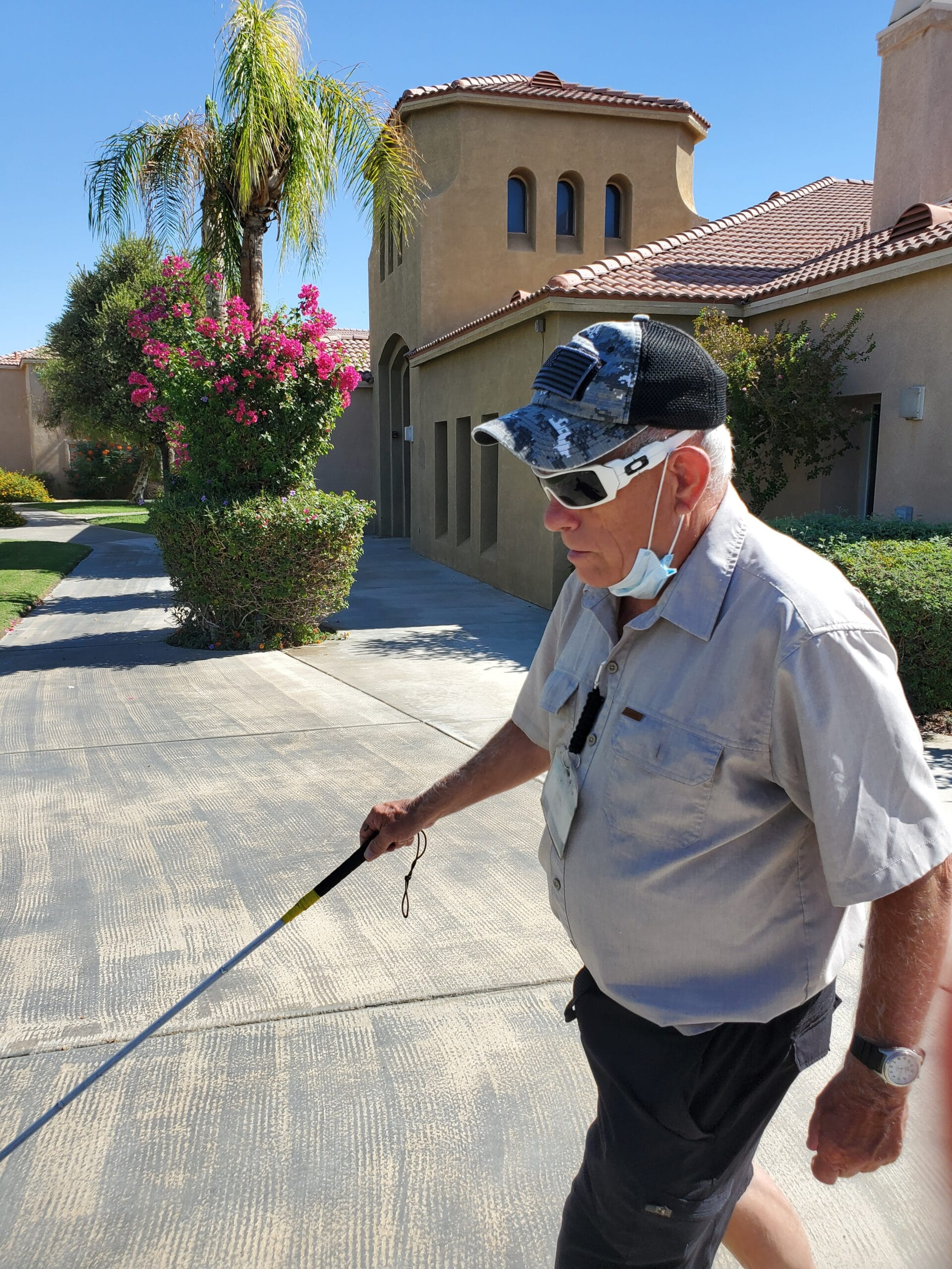 Photo of Jerry on the move walking on sidewalk with white cane.
