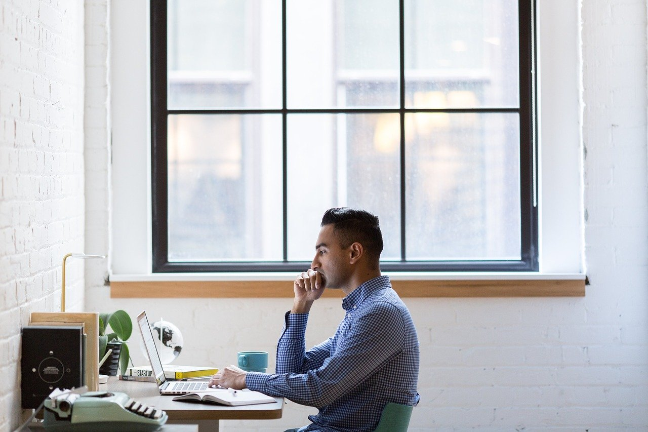 Man sit at desk with laptop. Large window behind him.