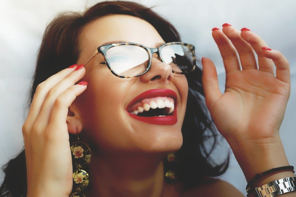 Woman with red lipstick smiling happy with her new glasses