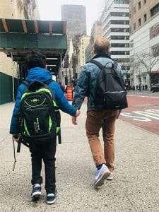 Teacher Jonathan guides a second grader on field trip through busy streets of Manhattan