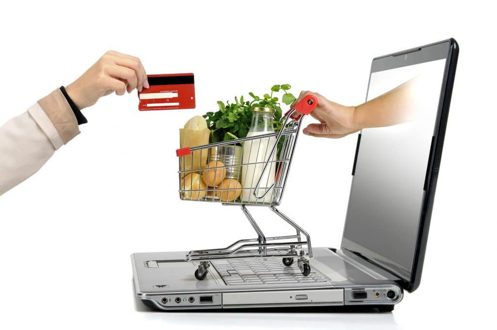 A grocery cart is being pushed through a laptop computer screen toward an outreached hand holding a credit card.