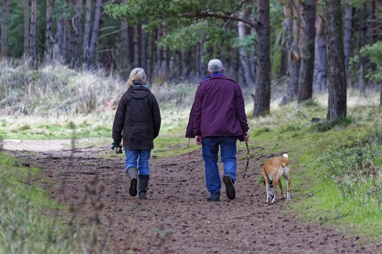 Older couple walking along a wide trail with dog