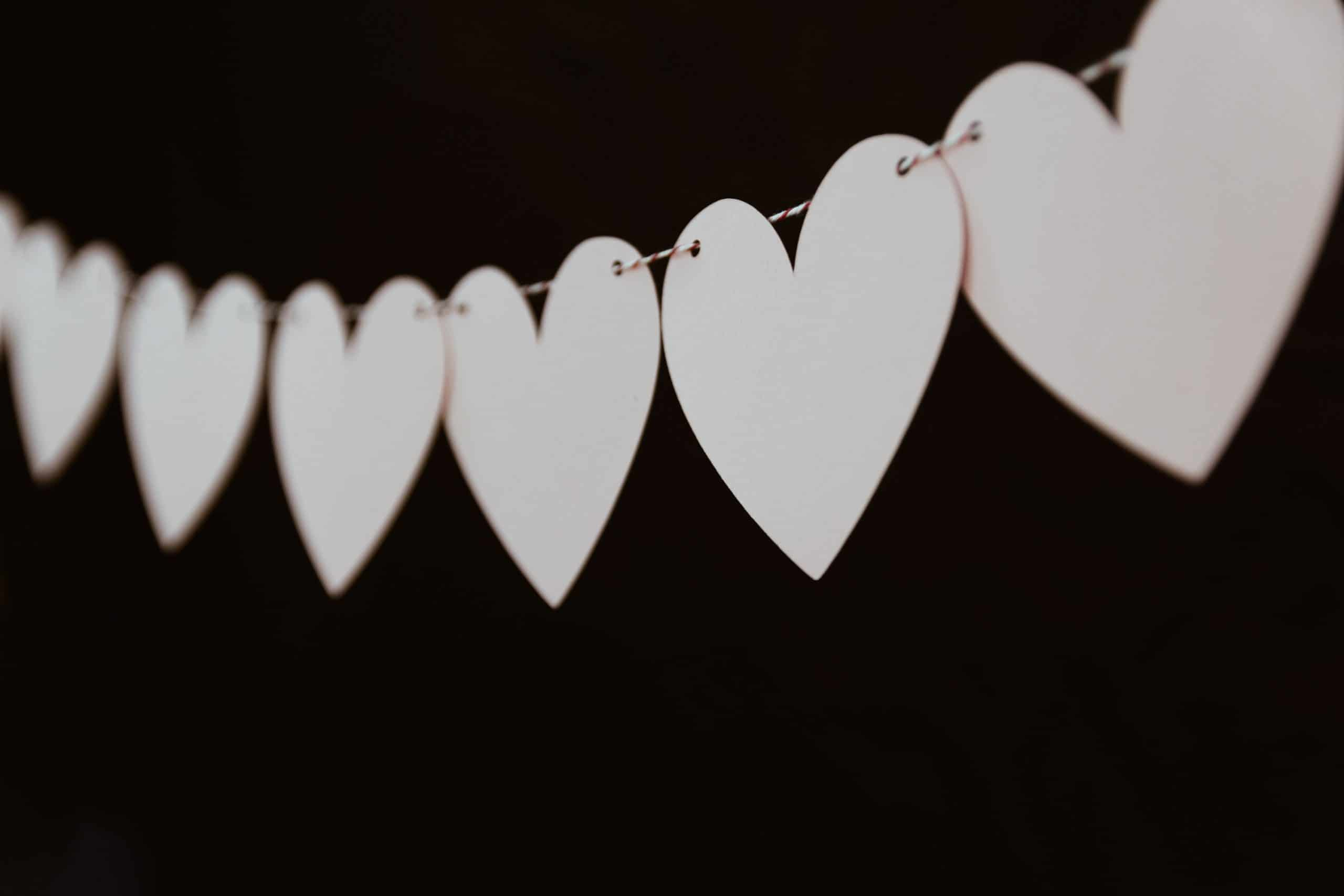 Picture has a string of white hearts on black background