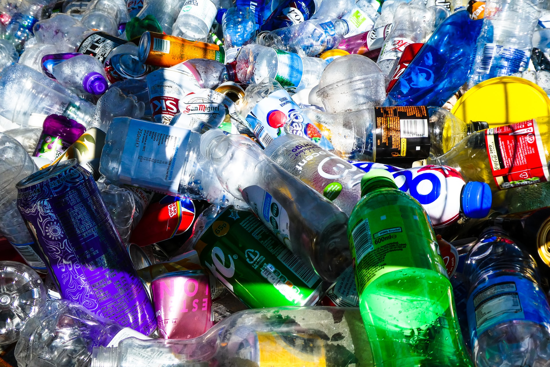 A pile of discarded plastic bottles, aluminum cans, and other garbage