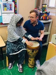 Student and teacher Jonathan play a drum together.