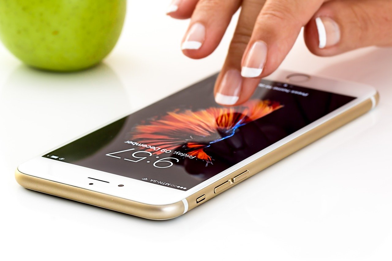 iphone resting on table with woman's hand touching screen