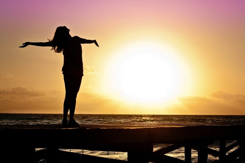 silhouette of woman standing on dock with sun set behind her.