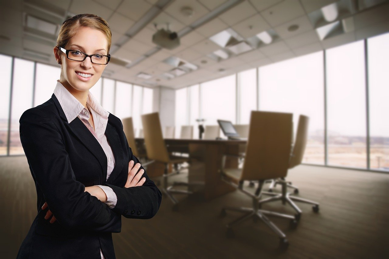 Woman in suit wearing glasses with board room behind her