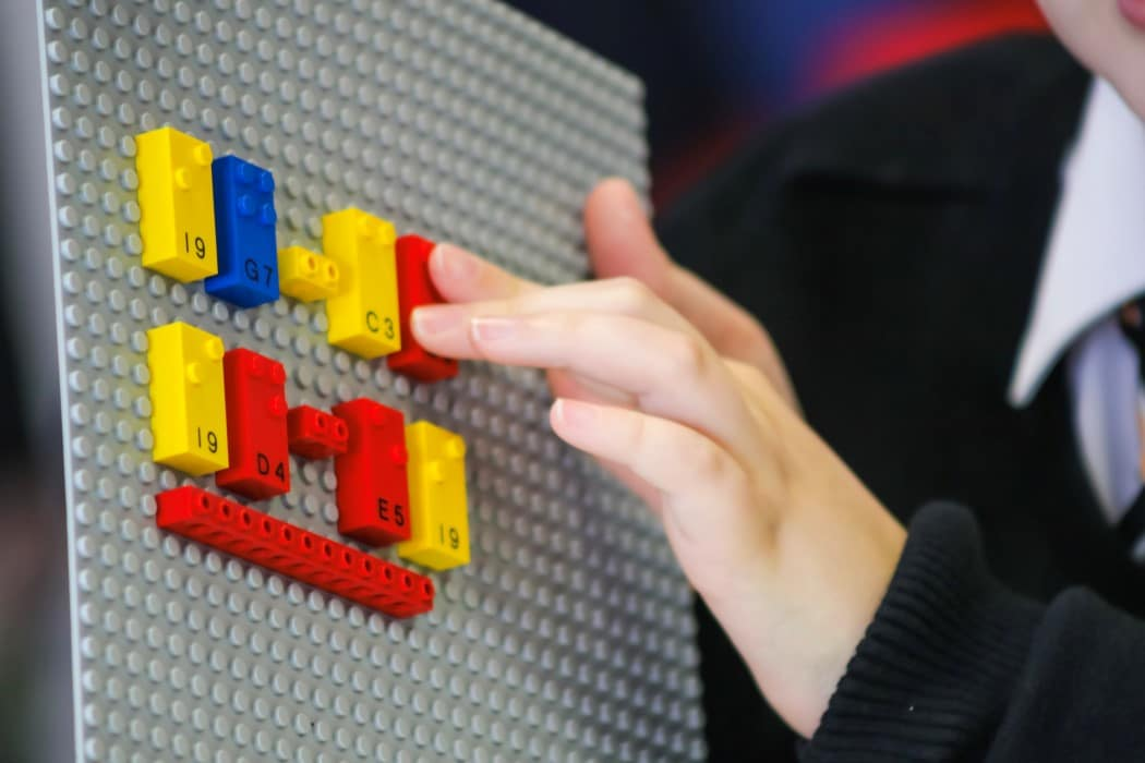 Flat lego board with various lego pieces on it being touched by youth.