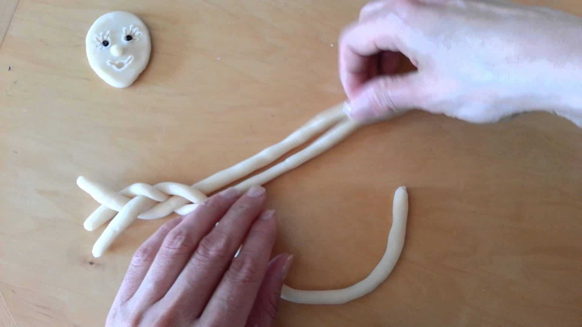 Hands mold salt dough into a braid on a table