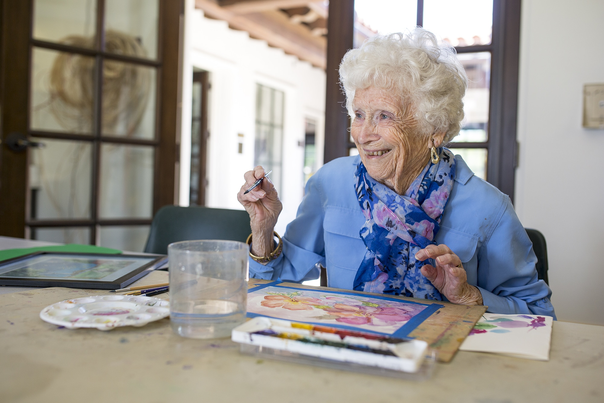 An elderly woman with a paint brush and painting in a Braille Institute art class