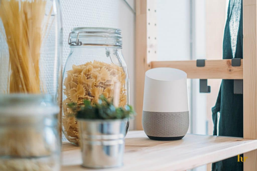 A smart speaker sitting on a wooden shelf next to jars containing dry pasta