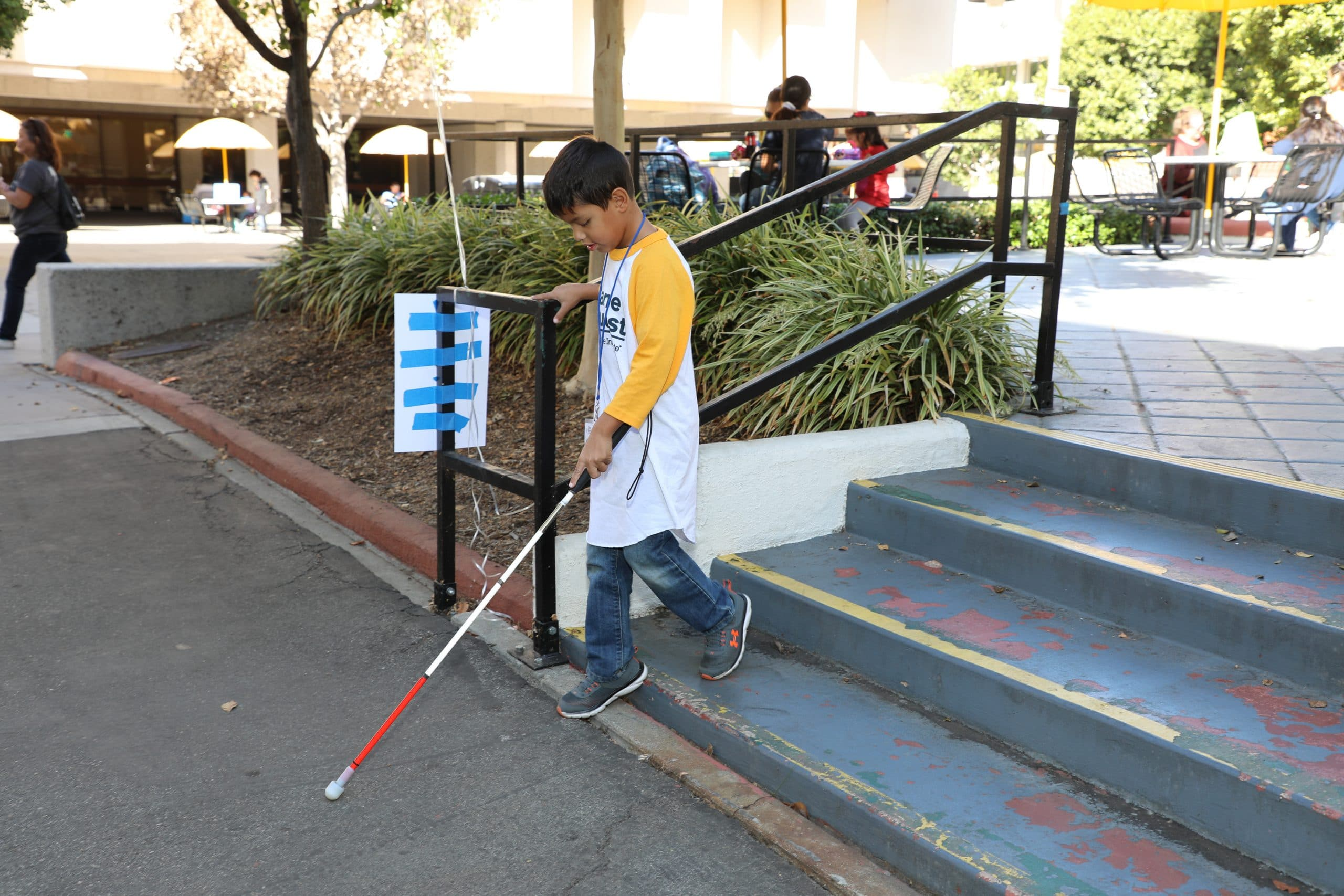 Young boy going down stairs with his white cane.