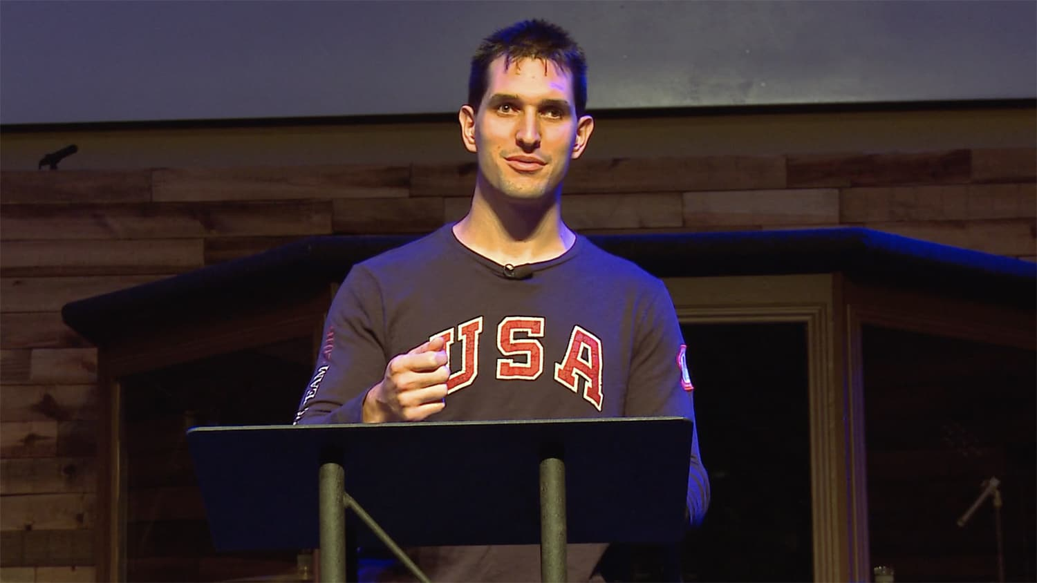 Tyler stands before a podium wearing a long sleeve shirt saying USA