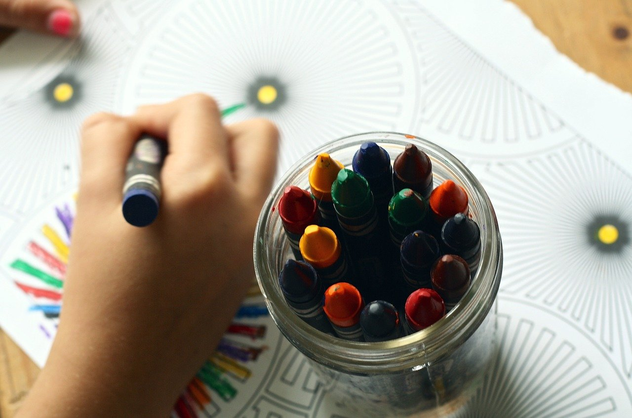 Child's hand coloring in the background, in focus is glass jar of crayons.
