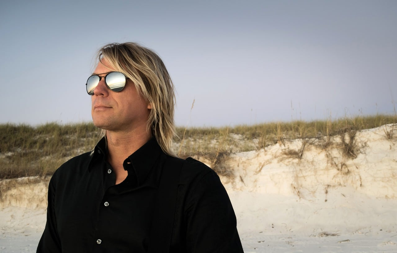 Man in black button down shirt wearing sunglasses, at the beach