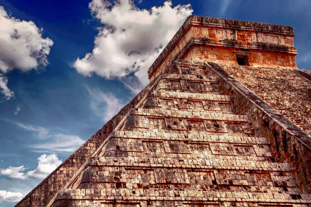 A close up of a Mayan temple against a blue sky with white fluffy clouds.