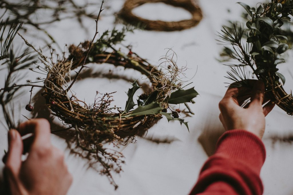 hands arranging twigs and plants in a wreath.