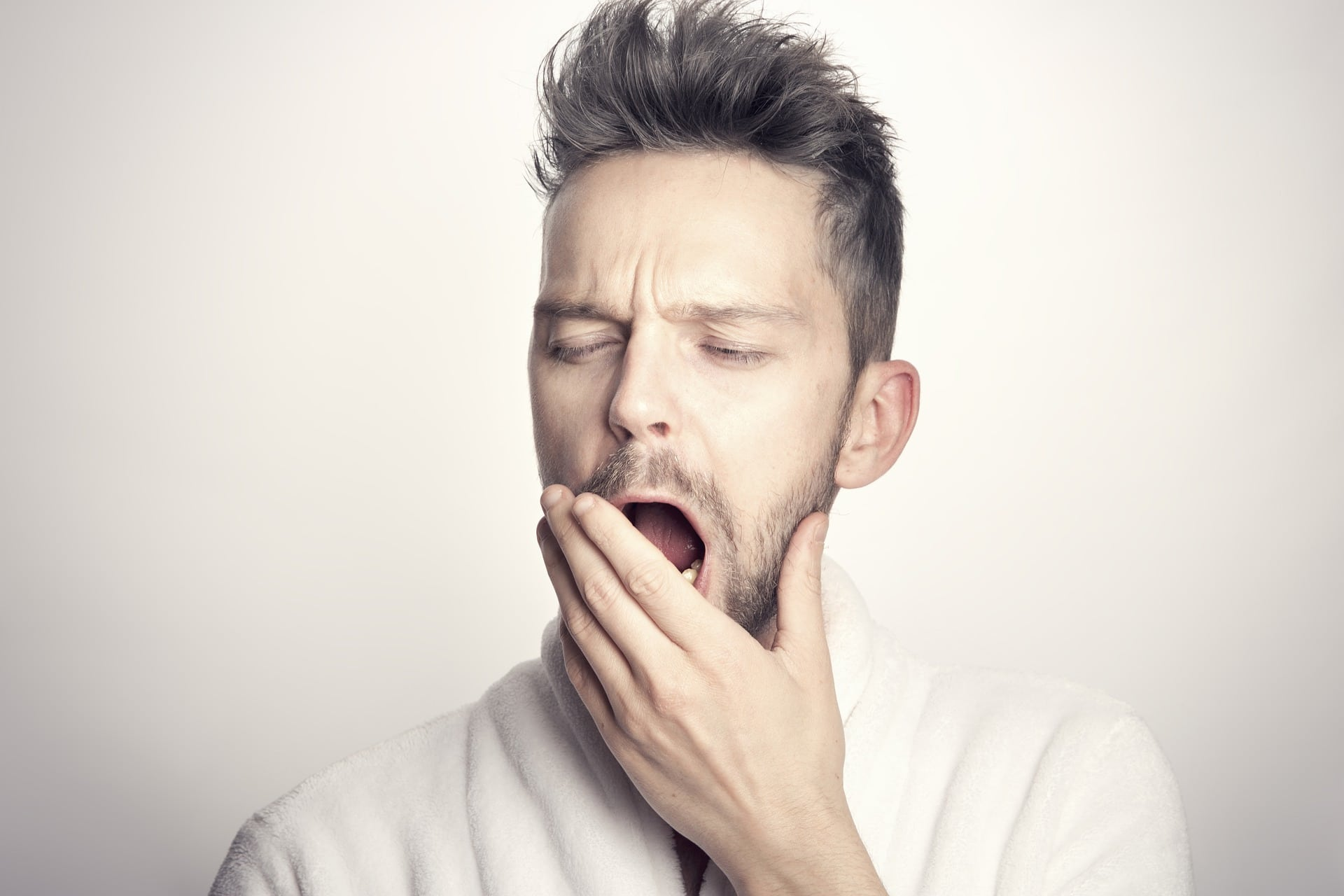Man yawning, his hand partially covering his mouth