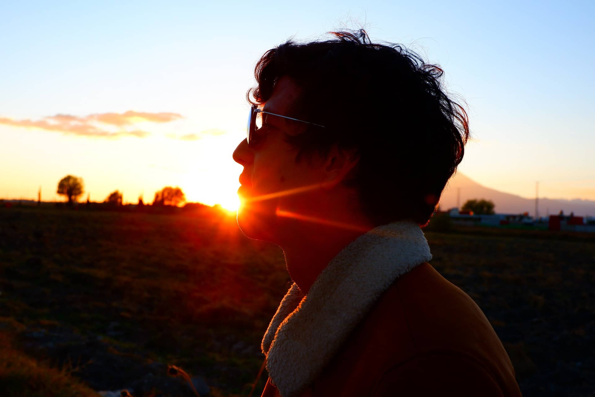 Man with glasses looking at sunset